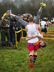 © Licensed to London News Pictures. 03/03/2019. Dorking, UK. Competitors take part in the 2019 annual Wife Carrying Race in Dorking, Surrey. Run over a course of 380m, with both men and women carry a 'wife' over obstacles, the race is believed to have originated in the UK over twelve centuries ago when Viking raiders rampaged into the northeast coast of England carrying off any unwilling local women . Photo credit: Ben Cawthra/LNP
