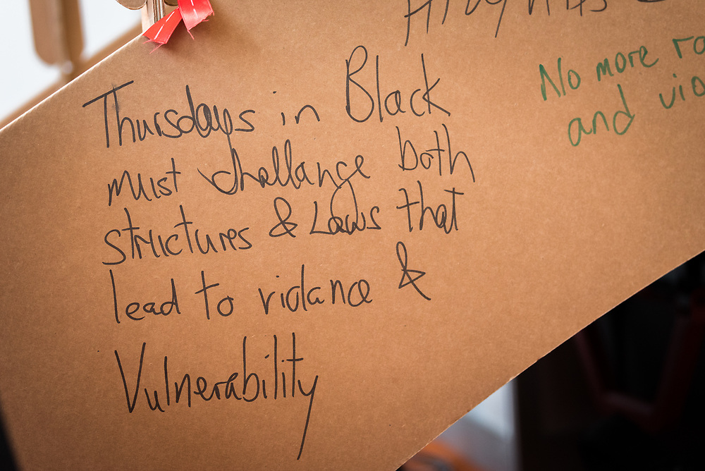 """26 July 2018, Amsterdam, the Netherlands: """"Thursdays in Black must challenge both structures and laws that lead to violence & vulnerability."""" After morning prayers in the Interfaith Networking Zone, religious leaders write messages on a symbolic bridge, expressing hopes and challenges for a coordinated response to HIV, particularly in view of the work against sexual and gender-based violence. The morning prayer was held on the theme of """"Faith against Gender based violence - Thursdays in Black"""". On 23-27 July 2018 in Amsterdam, the Netherlands, the World Council of Churches - Ecumenical Advocacy Alliance in collaboration with faith and other partners hosts an Interfaith Networking Zone in the International AIDS Conference's Global Village area, providing a dynamic space for exchanges, resources and workshops. The Global Village is an integral part and recurring feature of the International AIDS Conference, and offers an accessible venue intended to strengthen the connection between the international conference and the local hosting community."""
