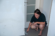 woman scrapes wall in preparation for painting