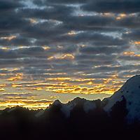 The sun lights up clouds as it rises over Peru's rugged Cordillera Vilcabamba.