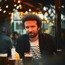 Cyril Dion, écrivain, réalisateur et militant écologiste, posant sur la terrasse du cafe Le Hibou. Paris, France. 22 fevrier 2019.<br /> Cyril Dion, writer, director and environmental activist, posing outside the Hibou cafe. Paris, France. February 22, 2019.