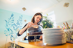 Young woman holding lid on cakestand in coffee shop, Freiburg Im Breisgau, Baden-Wuerttemberg, Germany