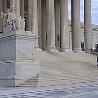 Tourists walk down the stone stairs of the U.S. Supreme Court building in Washington, DC.