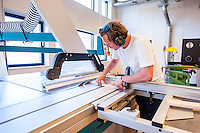 A cabinetmaking student cutting, finishing, and working on pieces of wood.