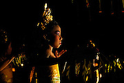 Young girls performing Balinese Legong dance, the Tari Panyebrama, outdoors at night. The tari Panyembrama is a dance for tourists; it came into being as some tourist hotels in Bali were welcoming tourists with the sacred tari Pendet, a dance traditionally reserved to welcome the gods, not tourists. Sanur, Bali, Indonesia