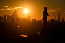 © Licensed to London News Pictures. 03/02/2019. London, UK. A man watches the sun rises from behind the City of London, from Primrose Hill in North London on a cold winter morning. Large parts of the UK continue to be deluged with snow and freezing temperatures. Photo credit: Ben Cawthra/LNP