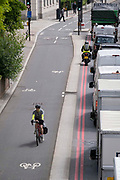 A cyclist rides westwards against the direction of queued traffic on Upper Thames Street in the City of London, the capitals financial district, on 22nd June 2021, in London, England.
