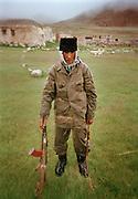 "Wooroochan Noor Ullah, Abdul Rashid Khan's son, the ""king"" of the Kyrgyz, on his return from patrolling the Tajik border at Kotal-Djamanang-shora, with his kalashnikov and horse wip. Qyzyl Qorum winter camp.<br /> <br /> Adventure through the Afghan Pamir mountains, among the Afghan Kyrgyz and into Pakistan's Karakoram mountains. July/August 2005. Afghanistan / Pakistan."