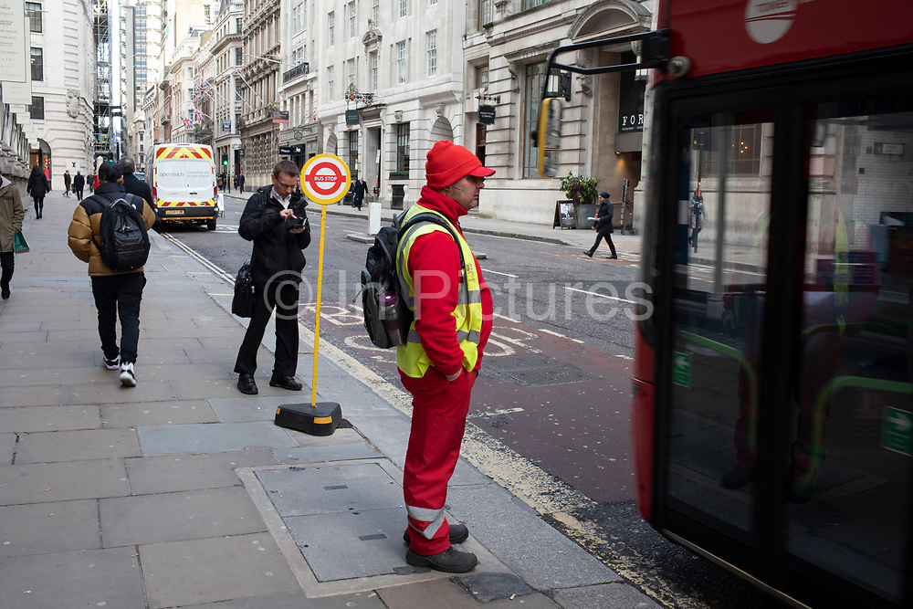 Council municipal worker waiting at a temporary bus stop in the City of London on 28th January 2020 in London, England, United Kingdom. The City of London is a historic financial district, home to both the great banking buildings. Modern corporate skyscrapers tower above the vestiges of medieval alleyways below.