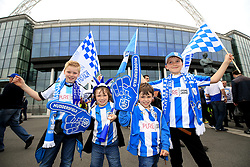 Young Huddersfield Town fans with flags, scarves and foam fingers in support of their team