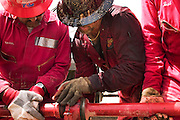 """Boots and Coots firefighters Bud, R., and Mike (C. covered in oil) help Halliburton pump driver (L., has company name covered with tape) connect pipes to """"sting"""" extinguished fire with drilling mud. A """"stinger"""" is a tapered pipe attached to the end of a long steel boom that is controlled by a bulldozer. Drilling mud, under high pressure, is pumped through the stinger into the well, stopping the flow of oil and gas. The Rumaila field is one of Iraq's biggest oil fields with five billion barrels in reserve. Rumaila, Iraq. Rumaila is also spelled Rumeilah."""