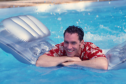 Man in a Hawaiian shirt floating on a raft in a swimming pool