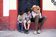 Two young boys sit with an elderly man on the sidewalk in Tlayacapan, Morelos state, Mexico on June 14, 2008.