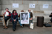 Rally organised by Stop the War coalition  in Trafalgar Square to mark 10 years of war in Afghanistan. A group sit on a bench listening to speeches.