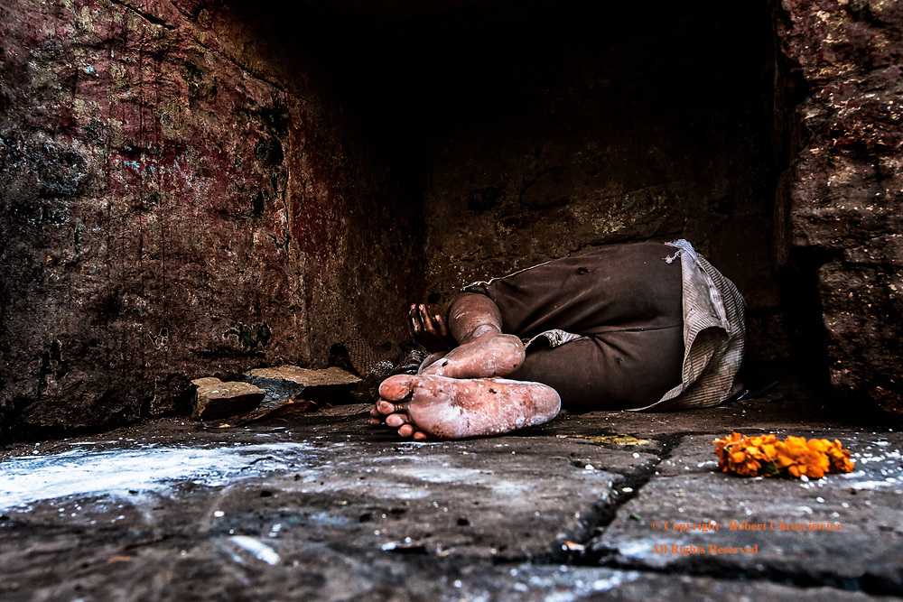 Alone at Last: A young homeless boy lies dead-asleep in an obscure, crypt like recess, underneath several feet of stone and the busy Dashaswamedh Ghat, near the river-side cremation Ghats, Varanasi India.