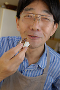 """Shoichi Uchiyama eating privet-hawk moth larva sushi.  Tokyo resident Shoichi Uchiyama is the author of """"Fun Insect Cooking"""". His blog on the topic gets 400 hits a day. He believes insects could one day be the solution to food shortages, and that rearing bugs at home could dispel food safety worries."""