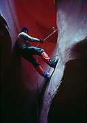 Jeff Gnass rappelling down dryfall in a slickrock slot canyon, Colorado Plateau, Arizona.  (LAW)