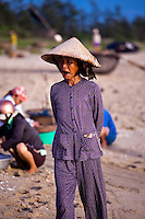 Old woman with a conical hat walking along China Beach in Vietnam.