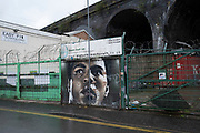 Street art of Mohammed Ali in Digbeth in Birmingham city centre which is virtually deserted under Coronavirus lockdown on a wet rainy afternoon on 28th April 2020 in Birmingham, England, United Kingdom. Britains second city has been in a state of redevelopment for some years now, but with many outdated architectural remnants still remaining, on a grey day, the urban landscape appears as if frozen in time. Coronavirus or Covid-19 is a new respiratory illness that has not previously been seen in humans. While much or Europe has been placed into lockdown, the UK government has put in place more stringent rules as part of their long term strategy, and in particular social distancing.