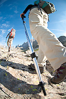 A young couple hikes through Titcomb Basin while backpacking in the Wind River Mountains of Wyoming (selective focus).