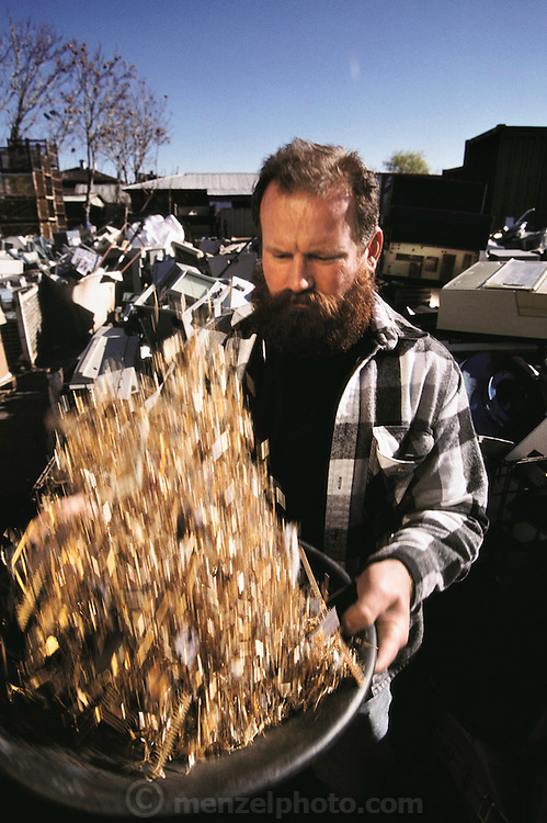 """Silicon Valley, California; Essential Elements computer recycling yard in San Jose. Owner and founder Bob Kaiser, seen here with a pan of gold plated parts recovered from computers, was a roofing contractor who panned for gold in California rivers on weekends until a friend told him """"there's gold in computers"""". He started by scavenging dumpsters and now runs a multi-million dollar business recycling computers for precious metals and for scrap sales to mainland China. (1999)."""