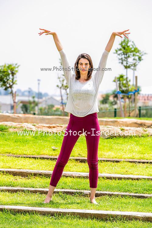 Young Woman makinYoung woman making her Yoga exercises in the park on the stairsg Yoga in the park Model release available