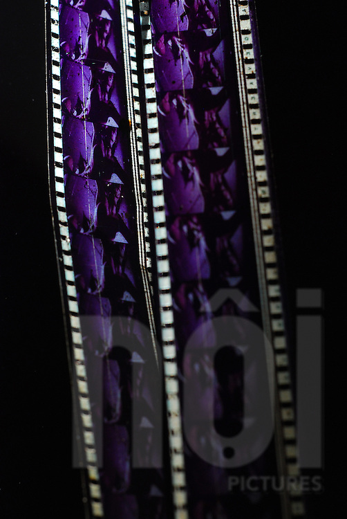 Strip of old film in abandoned cinema of Bouasavanh, Vientiane, Laos, Asia. A ray of light bring back vivid colors to the strip.