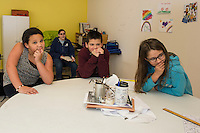 "Knevaeh, Xander and Eclapse work on solving the ""Riddle of the Day"" with senior program director Carly Migliore in the Senior Room at the Boys and Girls Club on Monday afternoon.  (Karen Bobotas/for the Laconia Daily Sun)"