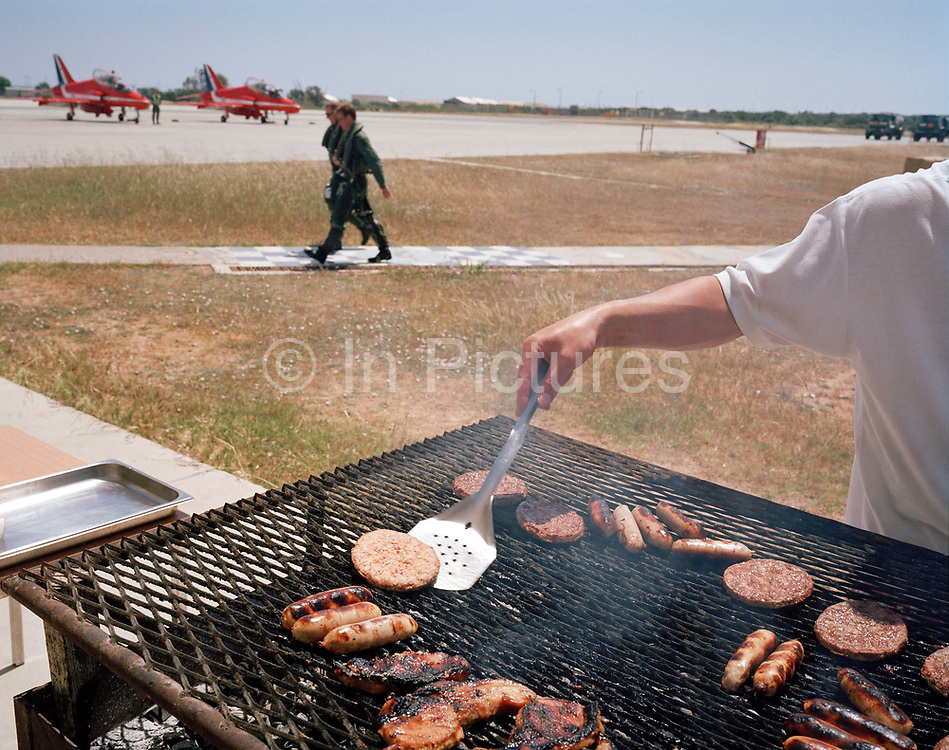 Anonymous chef prepares BBQ burgers and sausages as a pilot of the Red Arrows, Britain's RAF aerobatic team walks past. AN arm of an unseen cook places an uncooked burger onto the griddle in mid-day heat. While the team are operating out of this British-run base in southern Cyprus, every Friday lunchtime is dry-up time for the ground crews who support the aircraft and their pilots to maintain their airworthiness before the summer air show season.