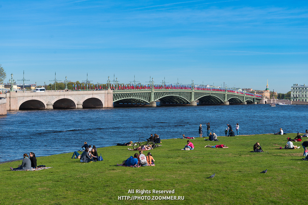 People Sit On A Grass Near Neva River And Troitsky Bridge, Saint-Petersburg