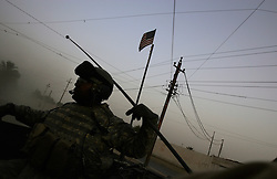 A sergeant with 4-14 Cavalry - a unit within the 172nd Stryker Brigade - rides a Stryker armored vehicle into the Baghdad Shiite neighborhood of Shula at dawn. The scene began another day of house to house searches - part of an operation by bolstered US and Iraqi forces in the hopes of getting a handle on the extraordinary numbers of sectarian killings in Baghdad - in Baghdad, Iraq on Sunday August 20, 2006. The brigade, which was in the process of rotating home at the end of a year tour in Mosul and northwestern Iraq, was diverted to the capital for an undetermined number of additional months.