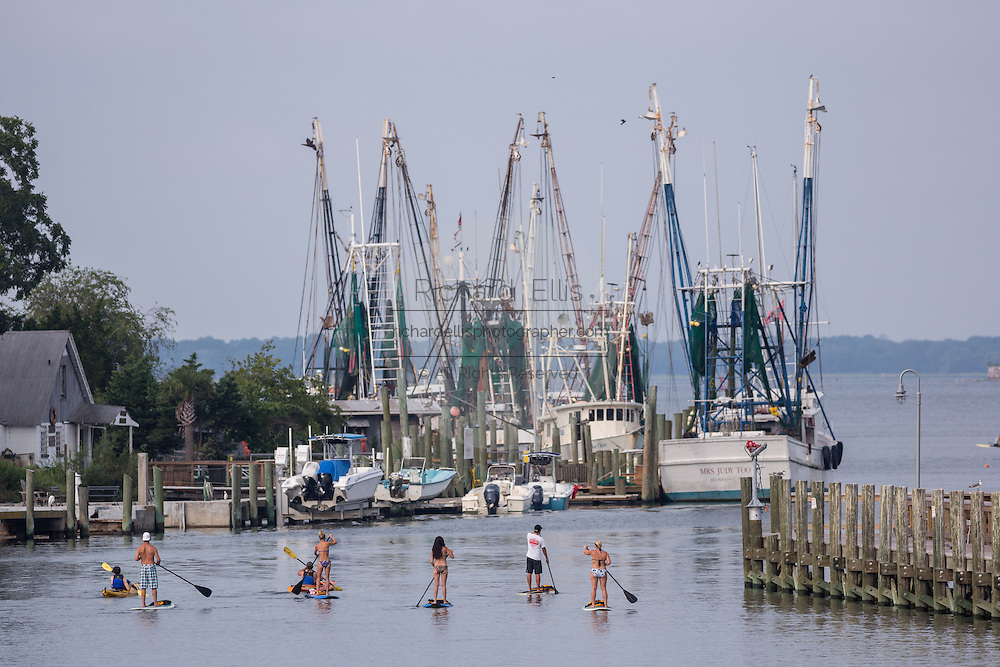 People use stand up paddle boards on Shem Creek in Mt Pleasant, SC.