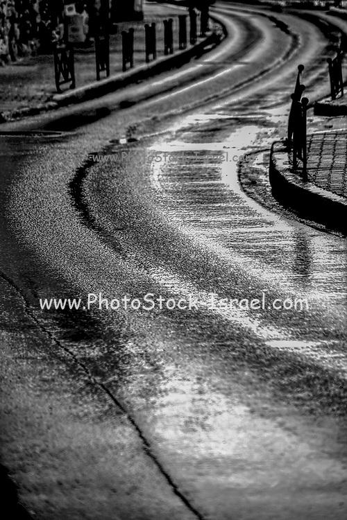 winding dark wet road. atmospheric image in black and white