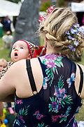 A mother holds her baby dressed in colourful clothes at the Standon Calling Festival in Hertfordshire, UK..Standon Calling is a small independent festival set among the hills in Herfordshire that showcases World Music, Indie Music and dance Music. It is one of the new, small and quirky boutique festivals which have become popular in the UK...