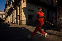 cuban man playing stickball in havana streets