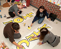 """(top right) Maddy Philpot, Lesie Dodd, Isabella Price and Federica Mattiazzi work on their """"Senior Pride"""" Lion King themed float Thursday evening for tomorrow's Homecoming parade.  (Karen Bobotas/for the Laconia Daily Sun)"""