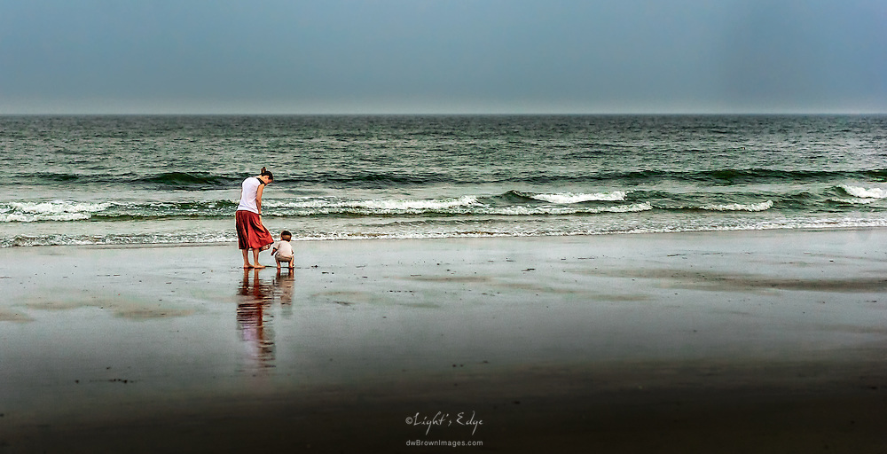A mother supervises as her child exploring the world at the beach in Ocean City,NJ.