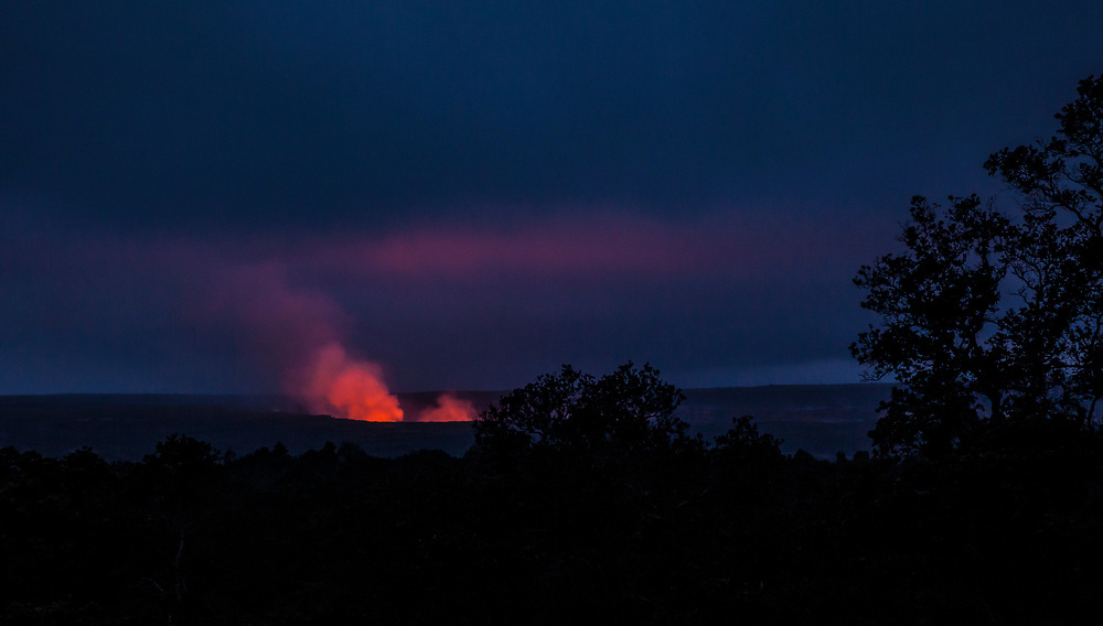 Kilauea Caldera glowing with billowing and rising gases and steam from the lava lake inside as seen from the kilauea Iki crater Rim trail, Hawaii Volcanoes national Park, Hawai'i, USA.