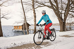 Mature woman riding bicycle on snow covered road, Bavaria, Germany