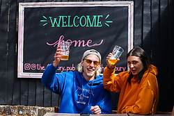 "© Licensed to London News Pictures. 12/04/2021. London, UK. Pub-goers enjoy a drink next to ""Welcome Home' sign at The Finsbury Pub, in Hackney, north London, which reopens after 4 months of Covid-19 lockdown. Cafes, restaurants, pubs, non-retail business and hairdressers across the UK closed following third national lockdown on 6 January, after a surge of coronavirus infections and hospital admissions across the UK. As restrictions are eased, cafes, restaurants, pubs, non-retail business and hairdressers reopen today.<br /> Photo credit: Dinendra Haria/LNP"