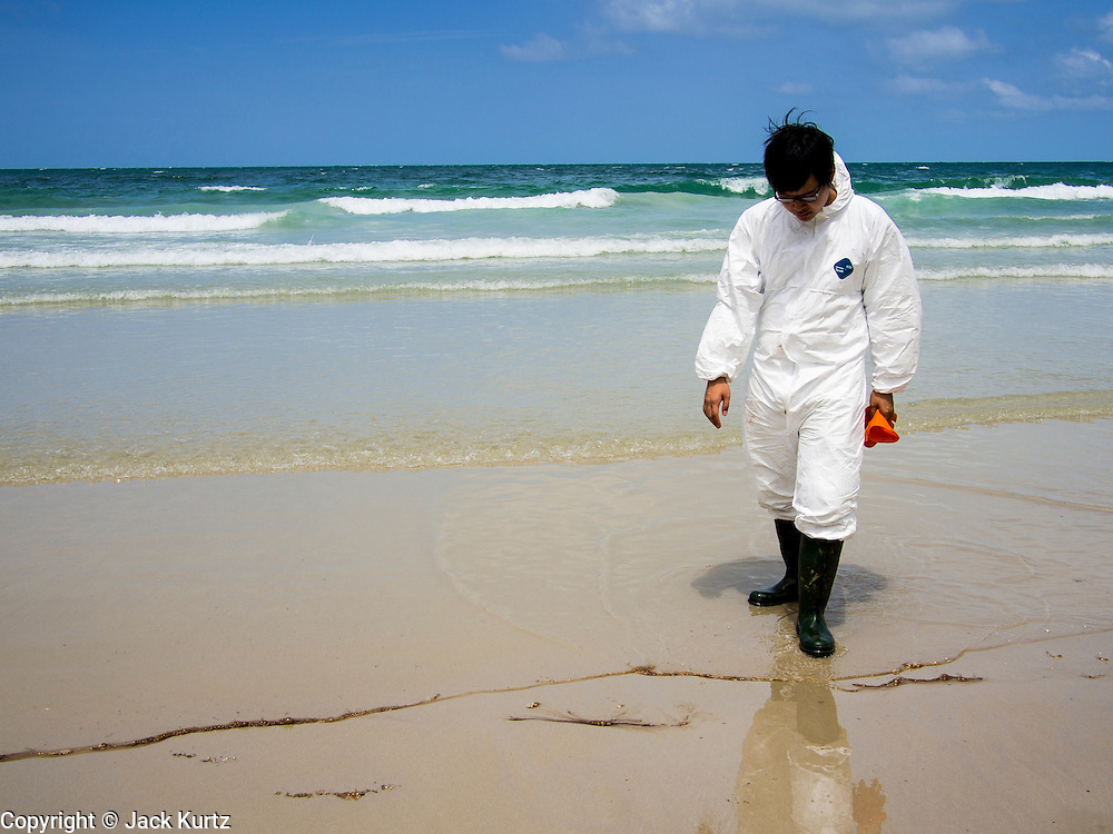 02 AUGUST 2013 - KOH SAMET, RAYONG, THAILAND: A cleanup workers looks at the tarballs that are washing up on Ao Prao beach after an oil spill fouled the beach. About 50,000 liters of crude oil poured out of a pipeline in the Gulf of Thailand over the weekend authorities said. The oil made landfall on the white sand beaches of Ao Prao, on Koh Samet, a popular tourist destination in Rayong province about 2.5 hours southeast of Bangkok. Workers from PTT Global, owner of the pipeline, up to 500 Thai military personnel and volunteers are cleaning up the beaches. Tourists staying near the spill, which fouled Ao Prao beach, were evacuated to hotels on the east side of the island, which was not impacted by the spill. Officials have not said when Ao Prao beach would reopen. PTT Global Chemical Pcl is part of state-controlled PTT Pcl, Thailand's biggest energy firm.    PHOTO BY JACK KURTZ