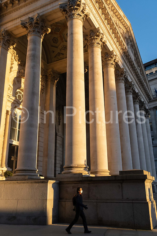 With most Londoners still working from home, a commuter walks beneath the columns of Royal Exchange while walking along a quiet Threadneedle Street during the evening rush-hour during the third lockdown of the Coronavirus in the City of London, the capitals financial district, on 26th February 2021, in London, England. At the top of Doric and Ionic columns with their ornate stonework, powerfully strong lintels cross, bearing the load of fine artistry and carvings which feature the design by Sir William Tite in 1842-1844 and opened in 1844 by Queen Victoria whose name is written in Latin Victoriae R. It's the third building of the kind erected on the same site. The first Exchange erected in 1564-70 by sir Thomas Gresham but was destroyed in the great fire of 1666. It's successor, by Jarman, was also burned down in 1838. The present building is grade 1 listed and cost about £150,000.