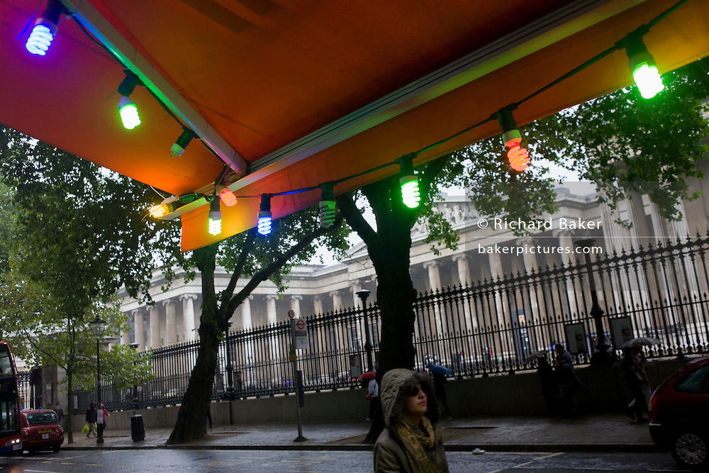 A woman walks beneath coloured lights during damp, gloomy weather opposite the British Museum in central London.