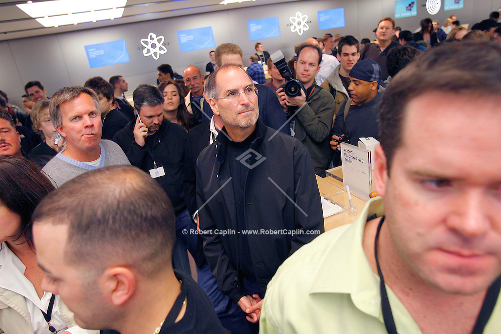 Steve Jobs, Apple Computer, Inc. chief executive officer, center, and Ronald Johnson, senior vice president of retail for Apple Computer, Inc., far left, stand inside the new Apple Store in New York on Friday, May 19, 2006. Apple Computer Inc., maker of the iPod music player, opened a 24-hour subterranean store in New York City, marking five years in retailing with an outlet built beneath a 32-foot glass cube.