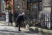 A male pedestrian attends to a loose shoe lace, on 10th April 2019, in Westminster, London, UK