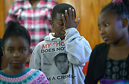 Sam Hill, 11, wipes away tears during a youth service at the St. Paul Missionary Baptist Church in Sanford, Fla., Sunday, July 14, 2013.  Many in the congregation wore shirts in support of Trayvon Martin following the not guilty verdict given to George Zimmerman, who had been charged in the 2012 shooting death of Trayvon Martin.(AP Photo/Phelan M. Ebenhack)