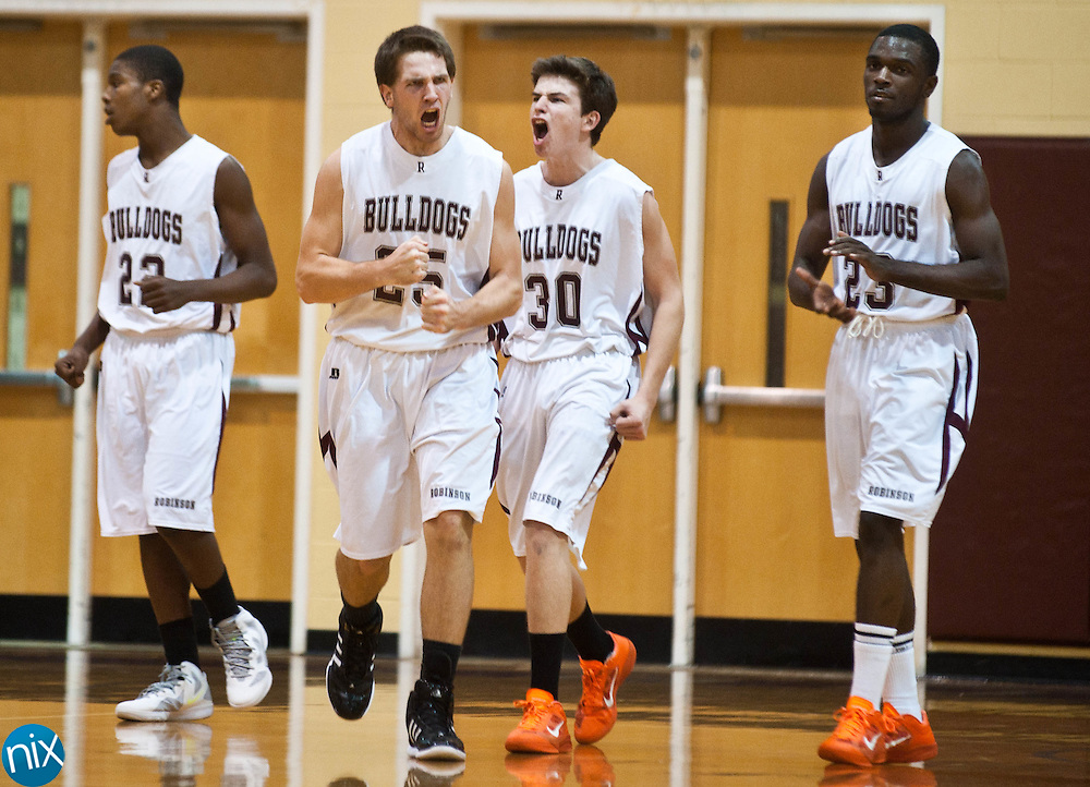 Jay M. Robinson's Brody Koerner (25), Kevin Anzenberger (30) and Elijah Hampton (23) celebrate a turnover as the Bulldgos took over the lead against Marvin Ridge Friday night in Concord. The Robinson Bulldogs won the game 73-64. (photo by James Nix)