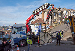 © Licensed to London News Pictures; 12/03/2021; Bristol, UK. A mural, 'Aachoo', by Banksy showing a woman coughing out her dentures on a wall in Vale Street during the Covid-19 coronavirus pandemic in England is removed by contractors with a crane. The house was in the process of being sold when the mural was painted on 10 December 2020. protective measures were installed on 23 January 2021. With a roughly 22-degree gradient incline, Vale Street in the Totterdown area of Bristol is said to be England's steepest street. Photo credit: Simon Chapman/LNP.