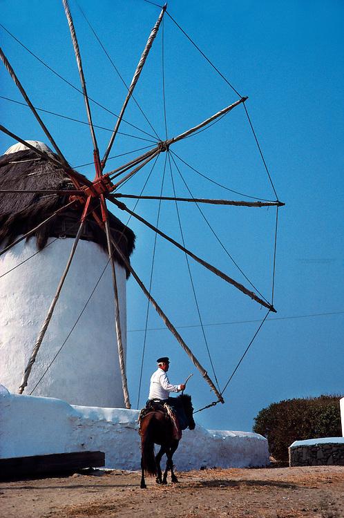 Greek man on horseback with windmill in background, Island of Mykonos, Greece