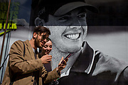 Young smiling couple pass a Nike retail poster of Northern Irish golfer Rory McIlroy, in central London. The young woman seems delighted with her selfie and smiles next to the sports hero's own rugged jaw and white teeth. The scene has a theme of smiles and smiling faces with the teeth of the British golfing hero, sponsored by the Nike brand.